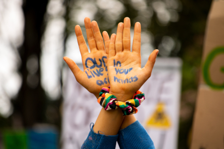 "Person's hands with the words ""our lives in our hands"" written on them"