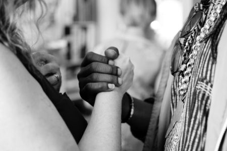 Black and white hands embracing