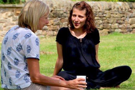 Two women sit in sun on retreat