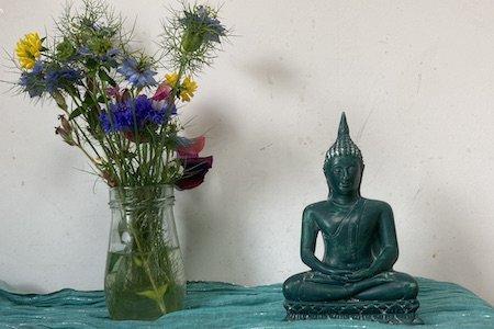 Wild flowers and Buddha Figure